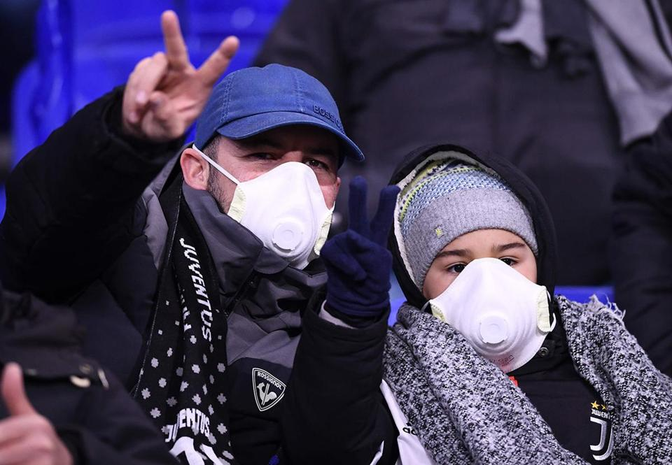 Juventus supporters wear protective face masks as a safety measure against the COVID-19 novel coronavirus at the Parc Olympique Lyonnais stadium in Decines-Charpieu, central-eastern France, on February 26, 2020, ahead of the UEFA Champions League round of 16 first-leg football match between Lyon and Juventus. (Photo by FRANCK FIFE / AFP) (Photo by FRANCK FIFE/AFP via Getty Images)