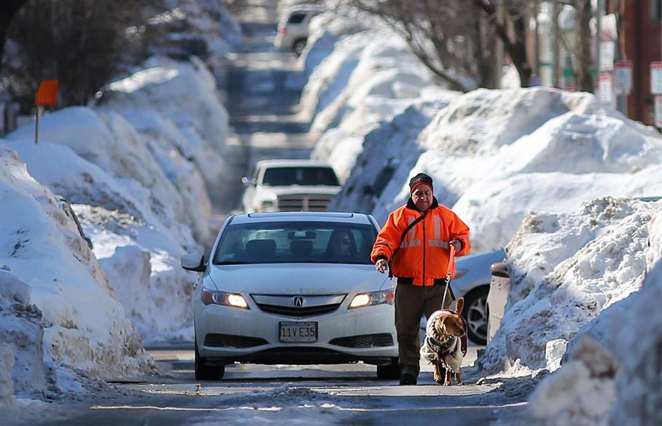 A man walked his dog down East Fifth Street in South Boston after a storm in February.