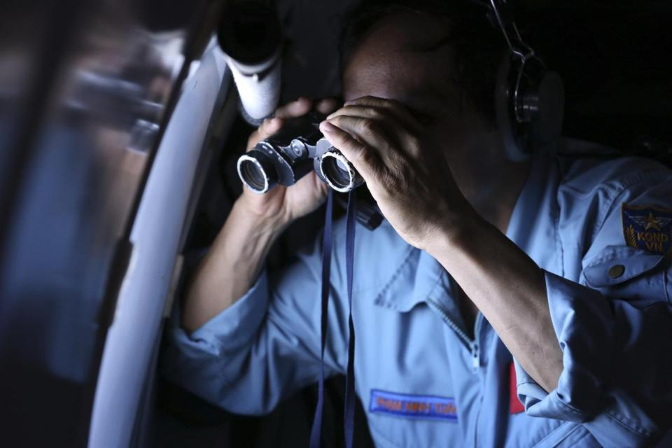 Vietnamese Air Force Col. Pham Minh Tuan used binoculars on board a flying aircraft during a mission to search for the missing Malaysia Airlines flight MH370 in the Gulf of Thailand.