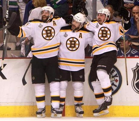 Vancouver, CA - 06/15/11 - Boston Bruins center Patrice Bergeron (37), Boston Bruins left wing Mark Recchi (28), Boston Bruins left wing Brad Marchand (63) celebrate Marchand's second goal of the night on an empty netter in the closing minutes of the 3rd period.The Boston Bruins took on the Vancouver Canucks in Game 7 of the NHL Stanley Cup Finals at Marchand's second goal of the game in the third period put the Bruins up 4-0. That drew a celebration among Bergeron, Mark Recchi and him (left to right) along the bench.