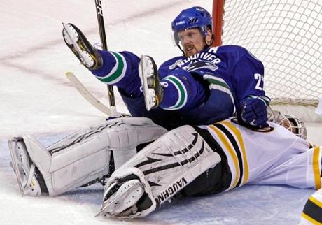 The Canucks' Daniel Sedin sits on Bruins goalie Tim Thomas after a collision in Game 1 at the Rogers Arena in Vancouver.