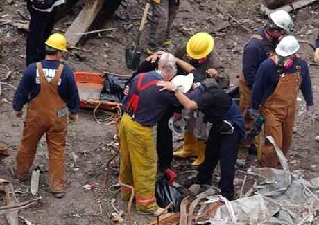 Rescue workers pray with a priest over human remains that were removed from the rubble of the World Trade Centers in New York, Thursday, Sept. 27, 2001. Behind them on the stretcher is another body that was pulled from the site. (AP Photo/Ed Betz)