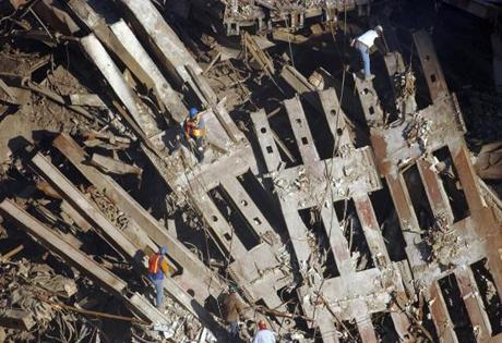 Workers climb over the remains of the World Trade Center complex in lower Manhattan, New York, Friday, Sept. 28, 2001. Workers continue clearing debris from the site of the September 11 terrorist attack on the World Trade Center towers. (AP Photo/Shawn Baldwin) -- Library Tag 09292001 National-Foreign AMERICA UNDER ATTACK