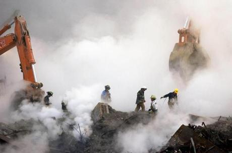 Firefighters make their way over the ruins of the World Trade Center through clouds of smoke as work continues at ground zero Thursday, Oct. 11, 2001, in New York, one month after the terrorist attacks on the Trade Center. (AP Photo/Stan Honda, pool)