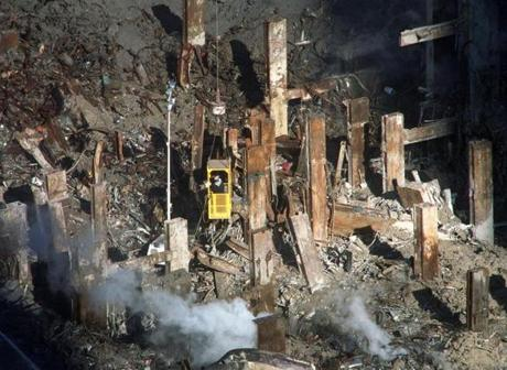 Sunlight filters into the still smoldering site of the World Trade Center attack highlighting the remains of Tower Two as workers riding in a basket suspended from a giant crane hover above, Saturday, Oct. 27, 2001, in New York. The round-the-clock recovery effort at the disaster site will come to a halt Sunday for a service to remember more than 4,000 victims of the Sept. 11 terrorist attacks. (AP Photo/William C. Lopez)NATIONAL AMERICA UNDER ATTACK - WORLD TRADE CENTER, NY