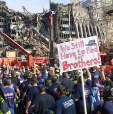 Firefighters rally at ground zero at the disaster site of New York's World Trade Center, Friday Nov. 2, 2001. Firefighters protested a plan to scale back the number of fire and police personnel searching for remains at the World Trade Center site. Some firefighters, who were among several hundred protesters, tangled with police who initially refused to allow them into the sealed-off area around the collapsed towers. (AP Photo/Stuart Ramson) -- Sign