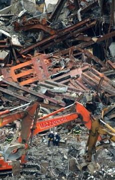Recovery workers look on as heavy machinery helps remove debris at the World Trade Center disaster site in New York, Saturday morning, January 12, 2002. (AP Photo/Robert Spencer) AMERICA UNDER ATTACK - WORLD TRADE CENTER DEBRIS
