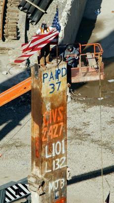 Workers unfold an American flag Saturday, May, 25, 2002, on top of the last standing beam at the site of the World Trade Center disaster in New York. The beam will removed from the site in a ceremony on May 30, officially ending the recovery effort. (AP Photo/Stephen Chernin) -- Library Tag 05262002 National-Foreign