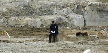 ARCHIVED TO THE BOSTON GLOBE LIBRARY SEPT. 19, 2002 Atr ground zero of the fallen World Trade Center towers, a lone police officer sits amid the rubble during a ceremony marking the one year anniversary of the attacks in New York on Wednesday, Sept. 11, 2002. (AP Photo/Amy Sancetta/POOL)