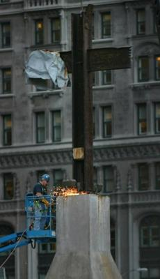 A worker dismantles the T-shaped steel beam, that gained fame as the ground zero cross, at ground zero of the World Trade Center site in New York, Thursday Oct. 5, 2006. The cross is temporarily leaving the World Trade Center site, the scene it has overlooked since being found by a construction worker amid smoking ruins two weeks after the Sept. 11 attacks. The artifact's new home will be three blocks north at the exterior wall of St. Peter's Church. (AP Photos/Bebeto Matthews) Library Tag 10062006 National/Foreign