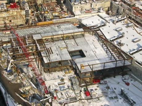 "The photograph shows that the sunken pool, which marks the site of 1 World Trade Center, is now almost entirely framed out in structural steel, except for its southwest corner. Along the walls now defined by a network of columns and beams, waterfalls will descend from plaza level to the pool surface. At the center of the main pool — and also visible in this picture — will be a secondary depression, or void, into which the water will cascade out of sight. Near the top of the picture, toward the left, one can see a wide swath of parallel diagonal lines. This marks the location of Fulton Street, under which a major east-west underground galleria will extend, linking the World Trade Center Transportation Hub with Battery Park City. Near the bottom of the picture is a bright red trailer or shed, almost perfectly cubic. To the right are two concrete forms looking like small ziggurats. These were footings for the 460-ramp that served the site since the early days of recovery. The photo illustrates why it was so important to dismantle the ramp recently, in order to allow construction of the memorial to proceed. credit: Port Authority of New York and New Jersey At the lower right corner of the picture can be seen the ""survivors' stairway,"" the last aboveground relic of the trade center, which stood on Vesey Street until last year. This structure will be incorporated into a staircase of the underground museum, although visitors will not be allowed to walk on it. Published 01-28-2009: Photo by Port Authority of New York and New Jersey"