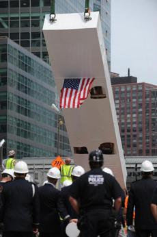 "Workers and officials watch as the historic ""Last Column,"" (covered in white) the final steel beam to be removed from the World Trade Center (WTC) site is returned August 24, 2009 for permanent installation in the 9/11 Memorial Museum at the WTC site in New York. The 36-foot high ""Last Column"" was covered in tributes from workers, rescue personnel and family members before the column was removed from the site, marking the end of the recovery efforts in May 2002. The Memorial Museum will be built around the column, here being raised from a flat bed truck before it is lowered into place. AFP PHOTO/Stan Honda (Photo credit should read STAN HONDA/AFP/Getty Images) Library Tag 08252009 National/Foreign"