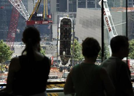 Tourists look on as the Fire Department of New York's (FDNY) Ladder Company 3 fire truck, which was responsible for evacuating civilians from the North Tower of the World Trade Center on September 11, 2001 is lowered 70 feet by crane in a ceremony July 20, 2011 to its exhibition space of the National September 11 Memorial Museum, which will open in September 2012. AFP PHOTO / TIMOTHY A. CLARY (Photo credit should read TIMOTHY A. CLARY/AFP/Getty Images)