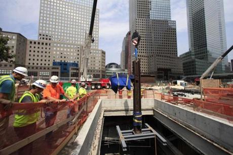 Construction workers lower the September 11 cross by crane into a subterranean section of the National September 11 Memorial and Museum on July 23, 2011 in New York City. The cross is an intersecting steel beam discovered in the World Trade Center rubble which served as symbol of spiritual recovery in the aftermath of 9/11. AFP PHOTO / POOL / Mark LENNIHAN (Photo credit should read POOL/AFP/Getty Images)