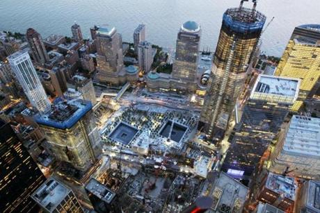 NEW YORK, NY - AUGUST 12: Construction continues on One World Trade Center (TALLEST BUILDING AT RIGHT) as the memorial footprints of the twin towers are seen (C) on August 12, 2011 in New York City. Upon completion, One World Trade Center will be New York's tallest skyscraper, topping out at a symbolic 1,776 feet, with 3 million square feet of office space. More than 2,700 people were killed when al-Qaeda terrorists hijacked U.S. passenger jets and flew them into the twin towers of the World Trade Center on September 11, 2001. Nearly ten years after the crippling attacks on Lower Manhattan, business, tourism and new construction like One World Trade Center have rejuvenated the formerly devastated cityscape.(Photo by Mario Tama/Getty Images) NYTCREDIT: Mario Tama/Getty Images
