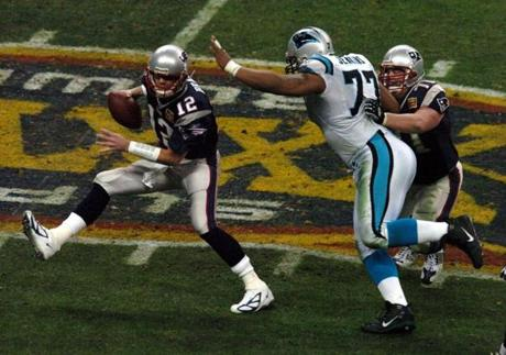 Brady, scrambling away from Panthers defensive lineman Kris Jenkins, had to evade considerable pressure from the Carolina defense.