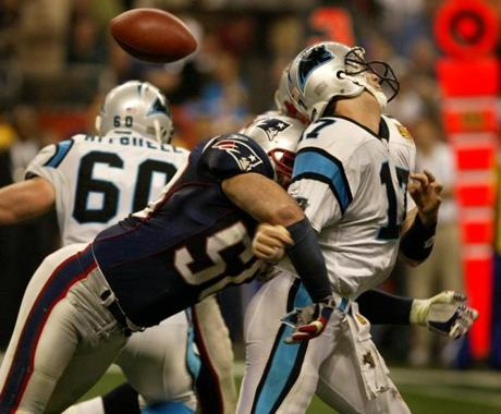 Patriots linebacker Mike Vrabel knocks the ball out of the hand of Panthers quarterback Jake Delhomme. The hit forced a fumble that was recovered by New England.