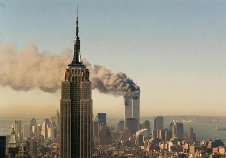 The twin towers of the World Trade Center burn behind the Empire State Building in New York, Tuesday, Sept. 11, 2001. In a horrific sequence of destruction, terrorists crashed two planes into the World Trade Center and the twin 110-story towers collapsed. Explosions also rocked the Pentagon and the State Department and spread fear across the nation. (AP Photo/Marty Lederhandler) finaledit 1