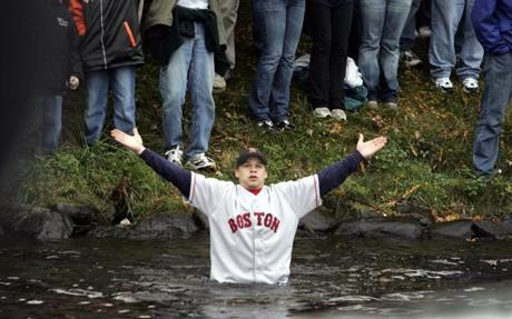 Another fan braved the water of the Charles on the overcast day with his clothes on as he tried to get close to the Red Sox.