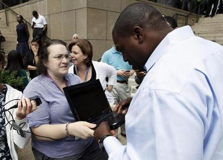 Kerry Schlueter (left) held a laptop computer for Damon Watts as he tried to find information on an earthquake that was felt in Baltimore.