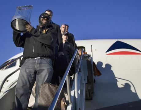Ortiz carried the trophy off the plane at Logan Airport.