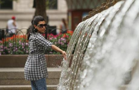 Johanna Escobar, of Boston, tests the waters while walking through the fountain Thursday at Copley Square.