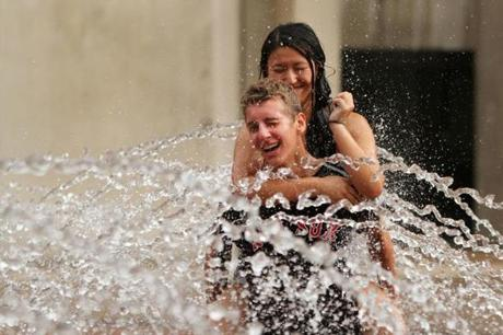 Tyler Sym, 14, gives Lee Katz, 14, both of Lexington, a piggy-back-ride through the water fountain Thursday at the Christian Science Monitor.