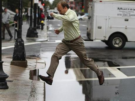 Pedestrians had to leap over a huge puddle at the corner of Clarendon Street and St. James Avenue in the Back Bay after a heavy morning downpour.