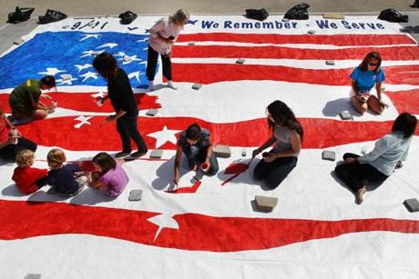 BVolunteers helped families and friends of  people killed on 9/11 to paint a 20-by 30-foot mural  in City Hall Plaza to benefit The Massachusetts 9/11 Fund.