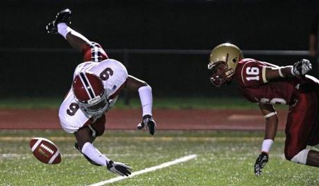 Devante Cartwright (9) of Brockton dived unsuccessfully for a tipped pass as Yosa Nosamiefan (16) moved in during first half action at Boston  College High School.