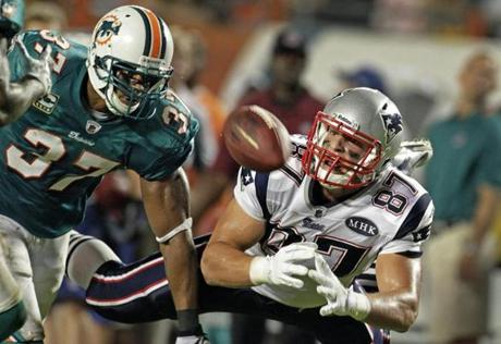 Patriots tight end Rob Gronkowski  (right) dived but couldn't  haul in a long second quarter pass from quarterback Tom Brady as Dophins defender Yeremiah Bell chased him down at Sun Life Stadium in Miami.