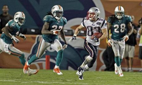 Patriots wide receiver Wes Welker (83) left a pod of Dolphins in his wake as he ran 99 yards on a pass from Tom Brady to score a touchdown in the fourth quarter at the Sun Life Stadium in Miami.