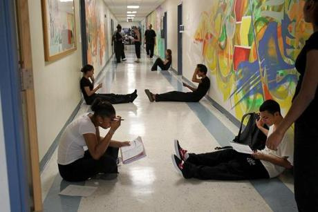 Mabel Francisco (left) and Ezequiel Lopez (right) worked in a hallway at Boston Arts Academy, whose building lacks space for rehearsal and other student needs.