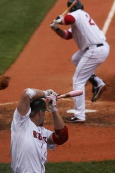 BOSTON, MASS- MAY 8. 2011-Globe photo by Stan Grossfeld--- Red         Sox third baseman Kevin Youkilis takes his practice swings as         Sox first baseman Adrian Gonzalezs steps into a single to center         during the third inning at Fenway Park on Mother's Day, May 8,         2011. Library Tag 05152011 Sports
