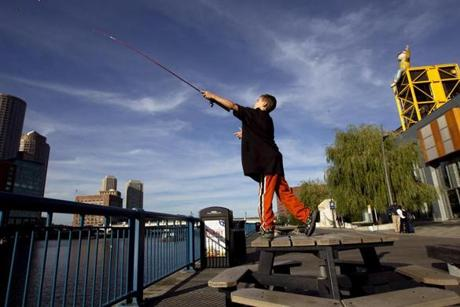 FOR METRO. Boston, MA 10/11/2011 Liam Walsh (cq), 8, casts his line while standing on top of a table with a brand new rod, while fishing with his family after a visit to the Boston Children's Museum in Boston, MA on Tuesday, October 11, 2011. The family also did some homework while waiting for the fish and had plans to eat dinner at the Barking Crab. (Yoon S. Byun/Globe Staff) Section: METRO Slug: n/a Reporter: n/a LOID: 5.0.426299454