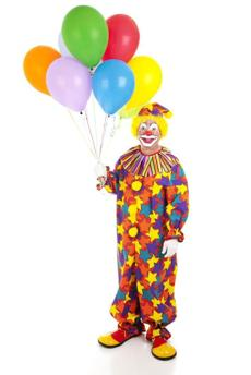 A clown holding a bunch of colorful balloons.