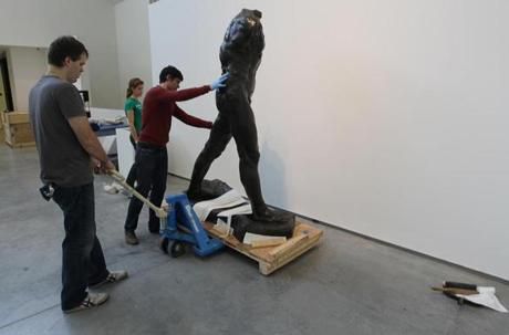 WELLESLEY, MA. 10/ 12 2011: In the gallery, fifth floor of the Davis Museum, L-R Andrew Daubar (cq), Kelley Tialiou (cq) and Mark Beeman (cq) move Auguste Rodin's WALKING MAN. At Wellesley College, The Reveal: Sculpture from the Davis Collections on view October 19,2011 are being set up on the top floor of the Davis museum with many items being moved from the basement. The works on view range feom the 1900 to 2006 from Rodin to Shonibare and many other artists.