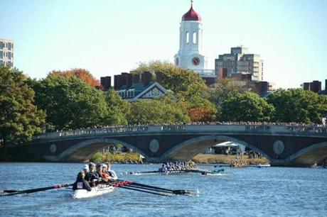 Spectators line up on bridges and river banks to watch the weekend-long Head of the Charles Regatta.