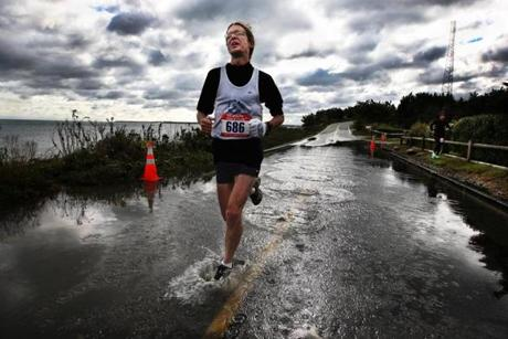 "Joseph Alfano, 45, of Holden, runs through a flooded course of         the Cape Cod Marathon. Said Alfano: "" The Cape Cod Marathon is a         hard race. It's got a lot of hills. It was a windy day right         after the big storm but also very beautiful. When I saw the         flooded road, it was not a big deal. You're about 3 miles out. I         thought, 'Come on, you've made it this far, you've got to keep         running. You can't go around it, you've got to get your feet         wet.' You've got to go a little crazy if you run a marathon. I'd         rather go straight for the finish line and not waste two steps         than stay dry. I've run this course seven times and its usually         beat me. But this is the one time I've run strong. I needed to         run it in 3:25 to qualify for Boston, and I ran it under 3:20.         It worked out. Post race I'm sore but it's a happy sore. Then         when I got home I didn't have a snow blower. All of Monday, I         shoveled for the entire day. I guess I like being sore."""