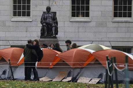 A cluster of tents near a statue of Harvard University founder John Harvard today.