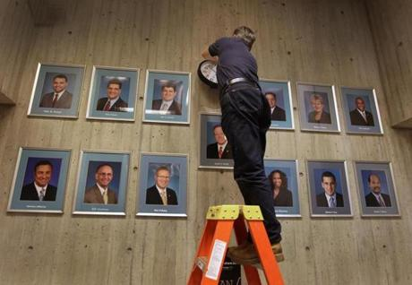 Walter Paluchowski replaced the clock above portraits of city councilors in the City Council offices at Boston City Hall.