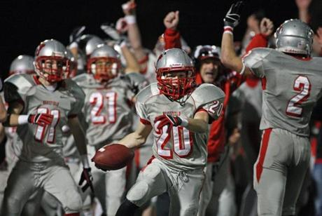 Bobby Wardwell (20) of Wakefield set off a celebration after he intercepted a pass in the final minute of the game for a 7-6 victory over  Marblehead at Manning Field in Lynn.