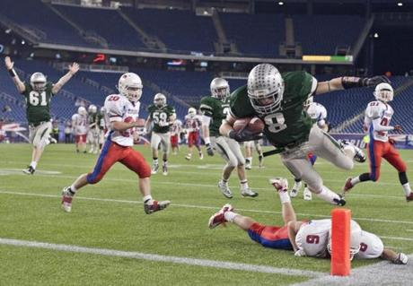 12/3/2011 Foxborough, MA Duxbury High's James Burke flies over Tewksbury High's Frank Mclaughlin (6) to score a touchdown during 4th quarter action of the Division 2 Super Bowl Championship at Gillette Stadium on Saturday December 3, 2011. (Matthew J. Lee/Globe staff) slug: 04duxtew section: sports Reporter: Anthony Gulizia