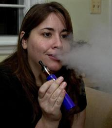 Valerie Schwaber, 29, of Lexington takes a puff of her favorite e-cigarette device, which includes a small vessel for holding the liquid that was made for her by another ''vaper.'' The plume looks similar to smoke but is nearly odorless and dissipates quickly.