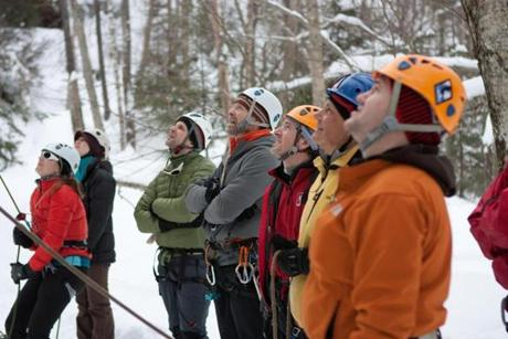for Travel - 29icefest - A group of climbers watches a guide lead climb an ice climb at Champney Falls. By leading the climb, the guide can set up a