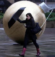 Boston, MA - 12-7-11 - A pedestrian walks in the rail past a giant ornament in front of the Prudential Center on Boylston Street. (Globe staff photo / Bill Greene) section:met,