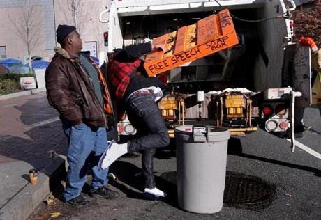 Boston, MA - 12-8-11 - Patrick Majid Doherty (cq) of Dorchester throws out a pallet in a garbage truck. He has been at Occupy since the beginning.The city has given Occupy Boston a midnight deadline to vacate. (Globe staff photo / Bill Greene) section:met, topic 09occupy