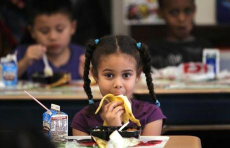 Boston, MA 11/16/11 First-graders, including Jennifer Frias (cq), 6, have lunch at their desks. Barney J. Brawer (cq), principal of the Michael J. Perkins School (cq), talks about the underchosen elementary school in South Boston, that is also a high achiever on the 3rd-grade MCAS. He gives The Boston Globe a tour, on Wednesday, November 16, 2011. (Pat Greenhouse/Globe Staff); Reporter: Vaznis; Section: Metro; Slug: XXX