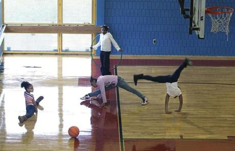 Boston, MA 11/22/11 Three cheerleaders practice their routines in the gym, during a class. Left to right, they are: Kayla DaRosa (cq), 8; Anaiyah Allen (cq), 9, and Shakeyah Parker (cq), 9. Another 3rd-grader Yuniq Thompson (cq), 8, is at top. Jeichael K. Henderson (cq), principal of the John P. Holland School, gives The Boston Globe a tour, on Tuesday, November 22, 2011. The Dorchester school has a number of facility perks and is making changes to improve its academic programs. (Pat Greenhouse/Globe Staff); Reporter: Vaznis; Section: Metro; Slug: XXX