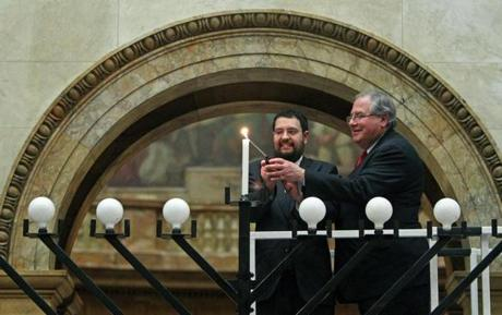 12-20-11: Boston, MA: Inside Nurses Hall at the Massachusetts State House, Rabbi Rachmiel Lieberman (cq,left) of Congregation Lubavitch Synagogue, and Speaker of the House Robert DeLeo take part in the ceremonial lighting of the Menorah. (Globe Staff Photo/Jim Davis) section:metro topic:14menora lighting photo